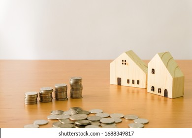 Selectove focus of Stack of money coin for saving for home, property with small wood house and calculator on the background. Wealth and saving plan for house mortgage. Personal investment concept.