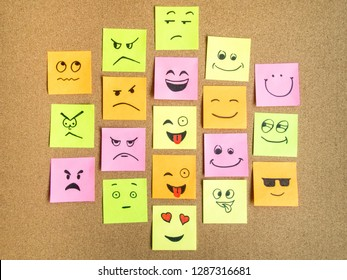 self adhesive office notes with different face expression on cork board as abstract concept photo