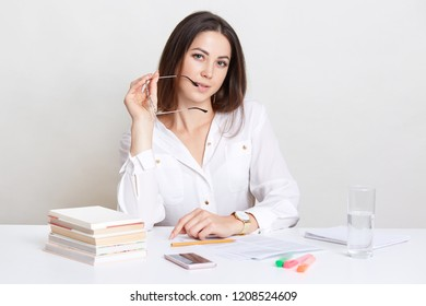 Self assured entrepreneur works in business documentation, keeps eyewear near mouth, prepares for business meeting. Beautiful student summarizes information after conductive lecture, sits at workplace