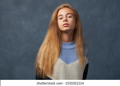 Self assured proud woman satisfied with own high achievements feels confident keeps head raised. Teenage girl with long thick blonde hair wearing warm woolen blue sweater isolated wall in Studio