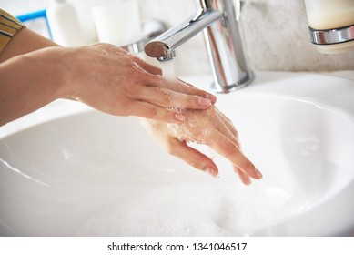 Self care and hygiene concept. Close up portrait of young woman with foam from soap washing her hands under tap water of basin