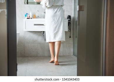 Self care and make up concept. Back side waist down portrait of young barefoot woman in white bathrobe staying in bathroom before mirror up of basin