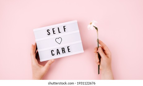 Self Care, Take care of yourself, wellbeing routine, self-care activities concept with open notebook, flower narcissus and female hand on pink background.