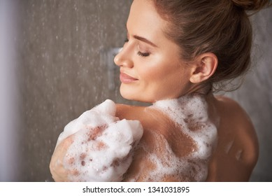 Self care treatment concept. Close up back side portrait of pretty smiling woman closing eyes while enjoying shower with foam at home
