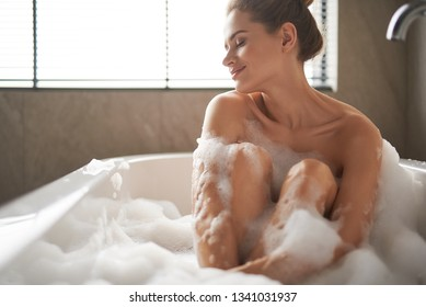 Self care treatment concept. Waist up portrait of young delightful woman closing eyes while enjoying relaxed foam bath at home interior