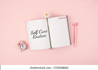 Self Care, wellbeing Routine, holistic set of self-care activities concept with open notebook, flower narcissus and alarm clock on pink background