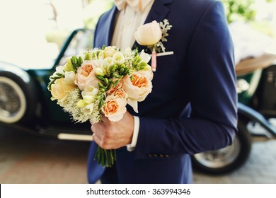 Self confident groom in a blue suit with a luxury bouquet of flowers standing near the wedding car on bright sunny day.