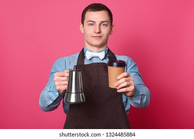 Self confident handsome male barista holds coffeemaker and disposable cup, prepares coffee, suggests to taste it, wears white bowtie, brown apron, isolated over pink background in coffeeshop