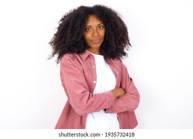 Self confident serious calm young beautiful African American woman wearing yellow jacket over white wall stands with arms folded. Shows professional vibe stands in assertive pose.