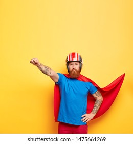Self confident serious superhero man has superhuman power, makes flying gesture, ready for flight and helping people, saves world, wears headgear, red cloak and blue t shirt, has brave behaviour