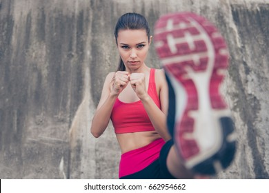 Self defence. Focus of a young cute serious fighter, training kickboxing high kick exercise with her foot, outdoors, in pink fashionable sport outfit, trendy sneakers