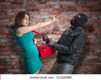Self defense concept. Young woman is fighting with thief and using pepper spray.