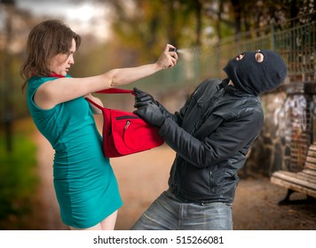 Self defense concept. Young woman was attacked by man in balaclava and is using pepper spray.