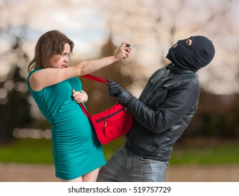 Self defense concept. Young woman is spraying with pepper spray on thief.