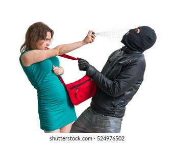 Self defense concept. Young woman is defending with pepper spray against thief or burglar. Isolated on white background.
