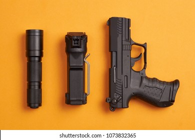 self defense gear - pistol, pepper spray and tactical flashlight on orange background