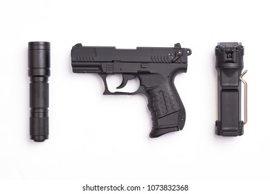 self defense gear - pistol, pepper spray and tactical flashlight on white background