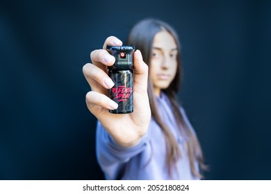 Self defense of young teenager girl with pepper spray. Isolated on dark background.