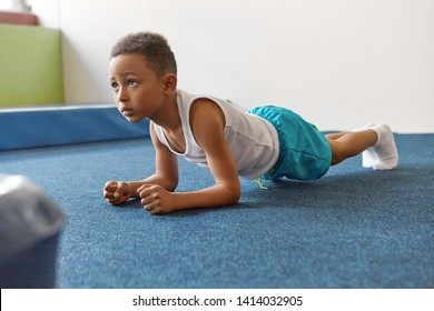 Self determined African American boy dressed in sports clothes planking at gym, feeling tired. Indoor image of black male kid doing elbow plank on floor at gym. Endurance and strength concept