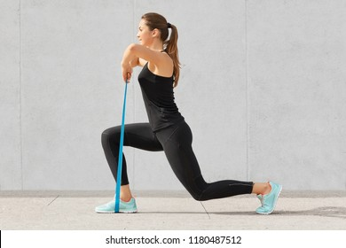 Self determined bodybuilder does exercises with rubber band, works on hands and legs, wears comfortable sneakers and sportsclothes, poses against grey concrete wall. Sport and goals concept.