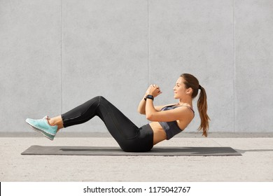 Self determined sporty woman with pony tail, dressed in leggings, top, sneakers, smartwatch makes on press, wants to have muscular body, has workout in in gym. People, gym and sport concept.