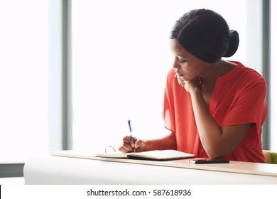 Selbstständige schwarze Unternehmerin beschäftigt sich mit dem Schreiben in ihrem Notizbuch, während sie an einem Schreibtisch mit einem großen hellen Fenster hinter ihr im Hintergrund saß.