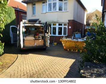 Self employed builder van with building tools & yellow skip full of rubbish situated near the house. Photo for background use as home renovation, investment project. Space to add text on driveway.