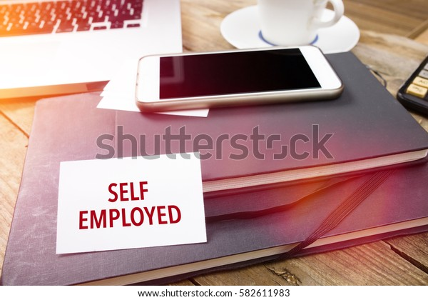 Self Employed on business card with text on office desktop with electronic devices, sun lit with lens flares.