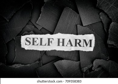 Self Harm. Torn pieces of black paper and words Self Harm. Concept Image. Black and White. Closeup.