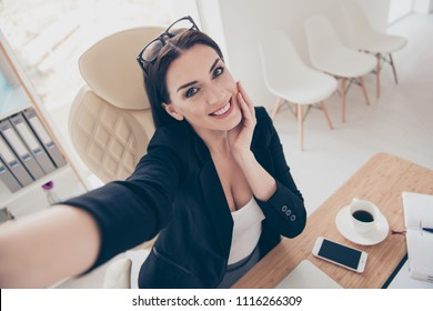 Self high angle view portrait of charming pretty accountant with spectacles on head shooting selfie on front camera during free time enjoying break having good mood sitting at desk
