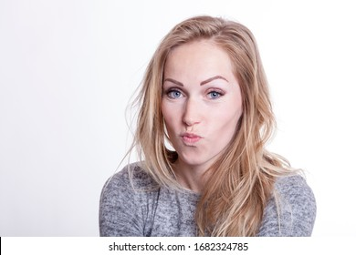 self ironic woman makes a duck face expression by pursing her lips. studio portrait of cute blonde with tousled hair isolated on white background