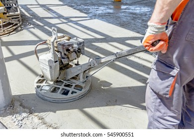 Self leveling power trowel machine, sander, for smoothing surface to finish concrete slab.
