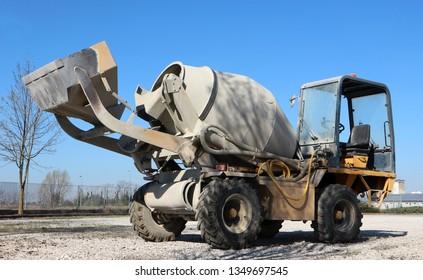 Self loading mini concrete mixer truck half covered of cement dust