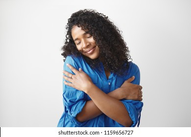 Self love concept. Isolated shot of beautiful pleased young dark skinned female with voluminous hairstyle embracing herself and closing eyes, enjoying soft fabric of her new stylish blue shirt