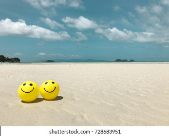 Self Made Hand Drawn Smiley Face on yellow ball with beach and blue sky background