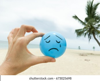 Self made hand drowning feeling blue sad face on blue ball with summer beach view