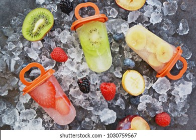 Self made popsicles with fruit pieces in it on ice