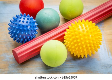 self massage and reflexology therapy concept - a set of small rubber balls and roller bar