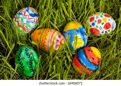 Self painted easter eggs on fresh grass. Colorful patterns and green grass bring true spring feeling.