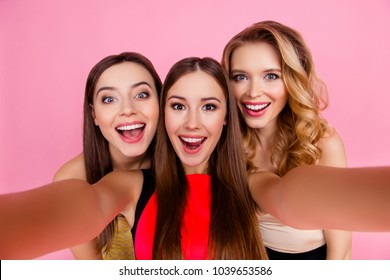 Self portrait of charming, funky, nice, attractive, pretty girls making selfie on smart phone  over pink background, with open mouths, laughing, screaming, shouting, glad, happiness