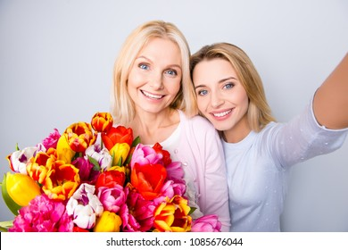 Self portrait of cheerful creative positive blogger shooting selfie on front camera with her grandmother having big colorful bouquet of tulips hugging bonding isolated on grey background