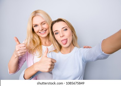 Self portrait of cheerful funny comic crazy funky cool mother and daughter shooting selfie on front camera gesturing thumbs up tongue out having good mood isolated on grey background