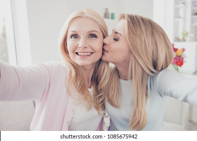 Self portrait of cheerful lovely cute charming daughter kissing in cheek mother family with one parent shooting selfie on front camera enjoying time meeting holiday day indoor