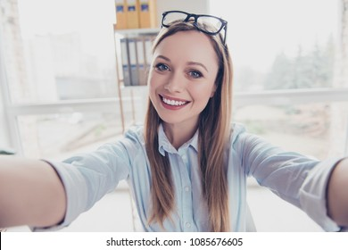 Self portrait of cheerful, positive, charming woman with hairstyle and glasses on head shooting selfie with two arms on front camera of smart phone in work place, station