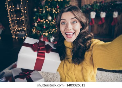 Self portrait of cheerful rejoicing girl shooting her gift box with christmas tree behind wearing yellow sweater
