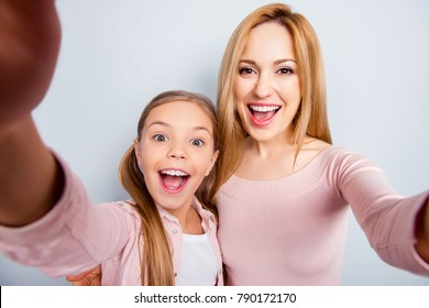 Self portrait of crazy, foolish mother and daughter with open mouth, laughing, together making selfie on mobile phone over gray background, spending, celebrate happy woman's day