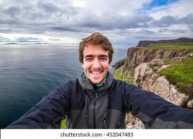 Self portrait at the edge of the world. Guy taking selfie on the cliff edge. Isle of Skye, Scotland