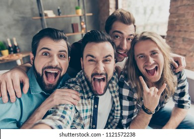 Self portrait of four attractive comic crazy funny foolish guys with hairstyle, showing tongue out and rock and roll symbol, making selfie on smart phone, front camera, sitting on couch in livingroom