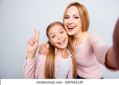 Self portrait of funny, comic, stylish, pretty, sweet mother and doughter, kid gesture v-sign, spending weekend, woman's day, standing over grey background
