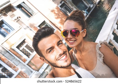 Self portrait of gorgeous couple in holiday, honeymoon in Venice, Italy - Beautiful smiling couple taking a selfie with smartphone in a beautiful and famous touristic place